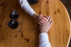 一个人的手有圆环的舒展到妇女` s手 玻璃红色二酒 浪漫晚餐,日期 coupl的手 免版税库存图片