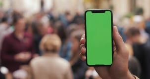 一个人的手的特写镜头拿着和使用绿色有一个垂直的绿色屏幕的屏幕流动小配件在街道上 股票视频