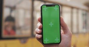 一个人的手的特写镜头拿着有一个垂直的绿色屏幕的移动电话在街道上 旅游电车在进来 股票视频