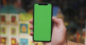 一个人的手的特写镜头拿着有一个垂直的绿色屏幕的移动电话在街道上 的儿童的商店 股票视频