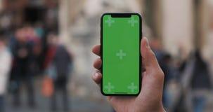 一个人的手的特写镜头拿着有一个垂直的绿色屏幕的移动电话在街道上 股票录像