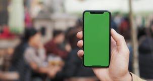 一个人的手的特写镜头拿着有一个垂直的绿色屏幕的移动电话在街道上 股票视频