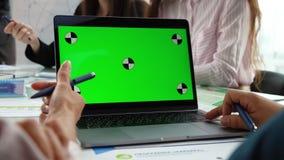 一个人的手的特写镜头运转在膝上型计算机的绿色屏幕上的 在背景中,人们坐在桌上和 影视素材