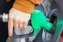 供以人员重新装满有燃料的汽车在汽油加油站 免版税库存图片