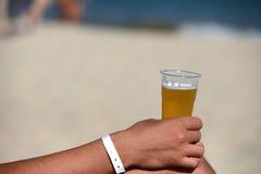 一个人的手的特写镜头用在海滩的刷新的啤酒 库存照片