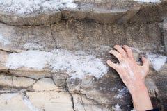 一个人的手紧贴对在石头的一个壁架 包括的岩石雪 库存图片