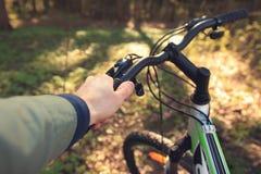 一个人的手自行车的轮子的 方向盘特写镜头 免版税图库摄影