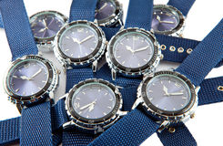 一个人的手表的大堆有蓝色拨号盘和蓝色的皮带在白色背景说谎 免版税库存图片