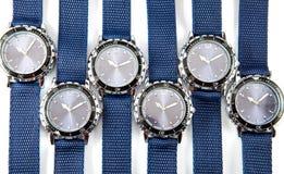 一个人的手表的等级有蓝色拨号盘和蓝色的皮带在白色背景说谎 库存照片