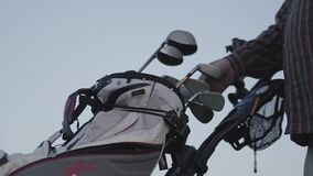 一个人的手采摘从俱乐部立场特写镜头的一家高尔夫俱乐部 打在高尔夫球场的人高尔夫球 ??  股票录像