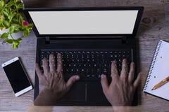 一个人的手transparents在计算机电话笔记本植物木桌里 免版税库存照片