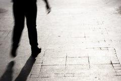 一个人的模糊的剪影和阴影在街道上的 图库摄影