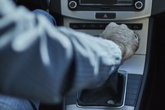 一个人的特写镜头一个汽车改变的齿轮的用他的手 免版税库存照片