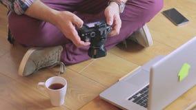 一个人的特写镜头坐地板在拿着照相机的膝上型计算机旁边 股票视频