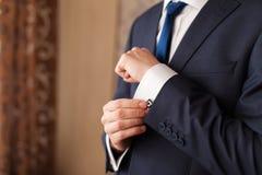 一个人的特写镜头改正袖子的黑衣服的 免版税库存照片
