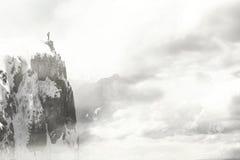 一个人的特殊片刻接触云彩的山的峰顶的 库存照片
