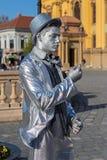 一个人的生存雕象,变成银色穿戴 免版税库存照片