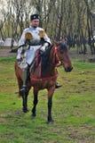 一个人的画象历史服装的,他骑一匹棕色马 库存照片