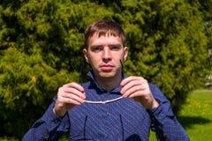 一个人的画象太阳镜和蓝色衬衣身分的外部在公园 免版税库存照片