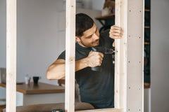 一个人的画象家庭衣裳的有一把螺丝刀的在他的手上在他的房子里修理一个窗口的木建筑 维修服务 免版税库存图片