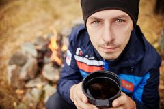 一个人的画象有一个杯子的热的茶在他的手上在森林火灾落 一顿野餐在森林里 免版税库存照片