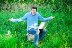 户外年轻人与杯子和膝上型计算机 库存图片
