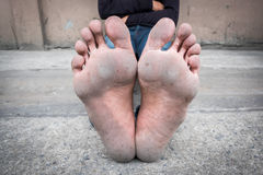 一个人的肮脏的脚坐水泥地板 免版税库存照片