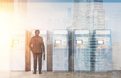 一个人的背面图在ATM机器附近的,城市视图 免版税库存图片