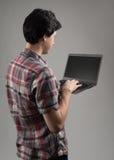 一个人的背面图有膝上型计算机的 免版税库存图片