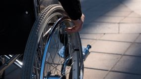 一个人的背面图轮椅的在与焦点的商业中心附近在手边 股票录像