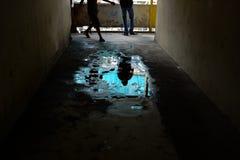 一个人的阴影一个水坑的在一栋老公寓 免版税库存图片