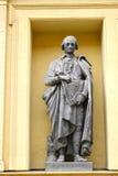 一个人的雕塑一个大厦门面的在圣彼得堡, Russi 图库摄影