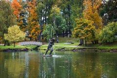 一个人的雕塑在一个湖中间的在秋天公园 库存照片