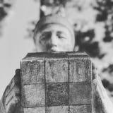 一个人的雕象在Kyiv,乌克兰的中心的拿着一个立方体 库存图片