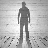 一个人的阴影在白色砖墙上的 免版税库存图片
