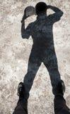 一个人的阴影打开在头的小舱口盖在水泥地板上 免版税库存照片