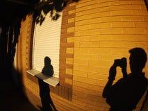 一个人的阴影有一台照相机的在有启发性墙壁上 库存照片