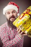 一个人的画象有拿着礼物的圣诞老人帽子的 免版税图库摄影