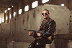 一个人的画象从之后启示世界的与机枪和黑玻璃在一个被放弃的大厦 图库摄影