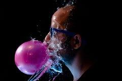 一个人的画象以太阳镜口香糖和是在面孔的被投掷的水 库存图片
