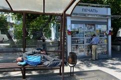 一个人睡觉在公共交通工具中止在莫斯科 免版税库存照片