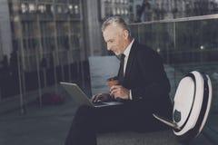 一个人研究膝上型计算机,坐栏杆 在他的单音轮子附近 免版税库存照片