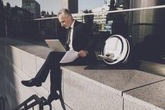 一个人研究膝上型计算机,坐栏杆 在他的单音轮子附近 库存照片