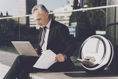 一个人研究膝上型计算机,坐栏杆 在他的单音轮子附近 库存图片