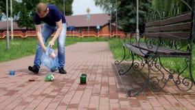 一个人穿过城市走并且收集在包裹的垃圾,无用单元收集,洁净的战斗机 股票视频