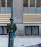 一个人站立与他的脚反对等待某人的路灯柱在布拉格,捷克-春天2019年 免版税库存图片