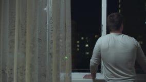 一个人站立靠近一个开窗口和神色在城市光 股票视频