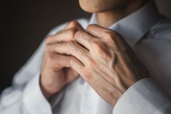 一个人紧固在他的衬衣的按钮 免版税库存图片