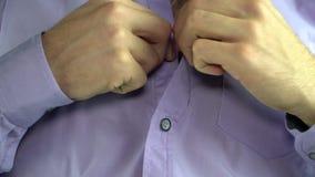 一个人紧固在衬衣的一个按钮 股票录像