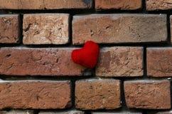 一个人编织了在粉碎的老红砖被构造的墙壁上的红色心脏 免版税库存图片
